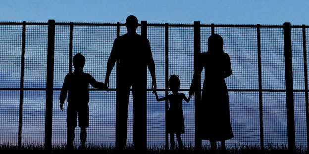 Immigrant Family By Chain Link Fence